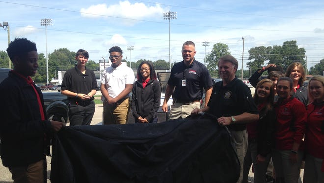 South Side High School students help unload equipment donated by Metro Narcotics investigators Wednesday morning.
