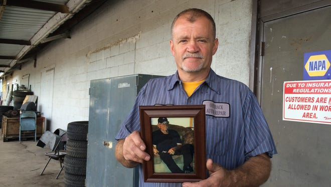 Mike Geller holds a photo of his late father, Ron Geller Sr., at his auto shop Friday, Aug. 26, 2016. Geller and his family were upset when ashes weren't returned in a timely way.