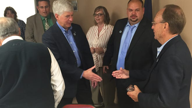 Gov. Rick Snyder, left, mingles with Sandusky community and business leaders Tuesday, Aug. 30, 2016, after a sit-down session in response to the state's Rising Tide program.