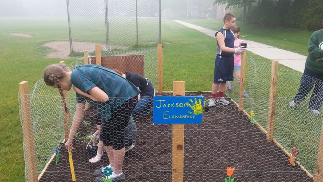 Anthony Holschbach and the Jackson Elementary School Environmental Club plants the new school garden.