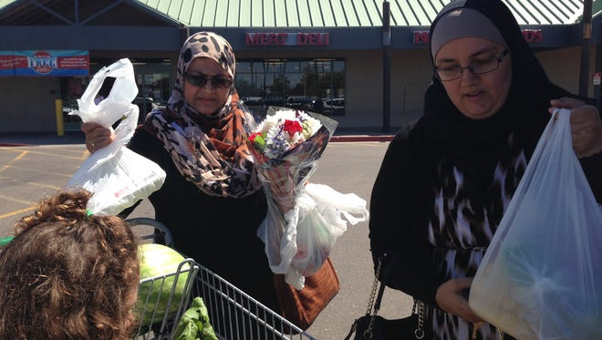 Kristy Sabbah of the Islamic Center of the East Valley and her family pack groceries and flowers for the refugee family into her van.