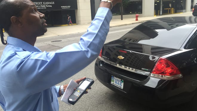 Detroit parking enforcer DeAndre (Ponytail) Hubbard points to a sign that says parking is restricted to city vehicles, yet someone who wasn't a city employee parked on Larned Street near the Coleman A. Young Municipal Center on Wednesday, Aug. 31, 2016. The person got a $45 parking ticket.
