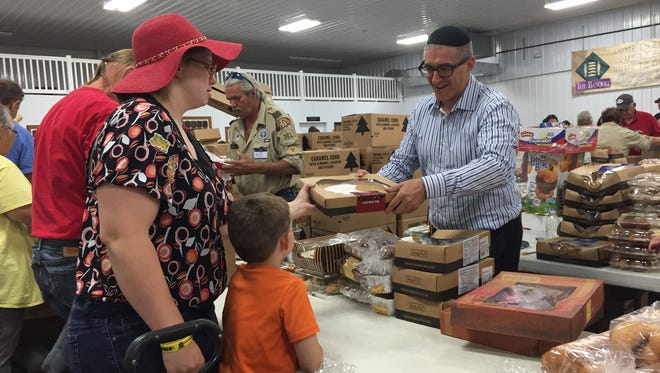 """Rabbi Pesach Wolicki of Efrat, Israel hands out a pie to Donrina Maddy and her son, Gary Maddy III, on Friday, Sept. 2, 2016. Wolicki is in Sioux Falls to promote """"Blessing Bethlehem,"""" a program modeled in part after Faith Temple's weekly food giveaway."""