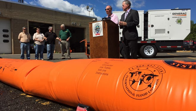 From right, Rockland County Executive Ed Day and Chris Jensen, program coordinator for Rockland's Office of Fire and Emergency Service, demonstrate water barriers acquired by the county. The barriers are a tool to combat flooding.
