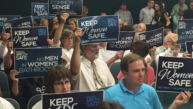 """Residents opposed to adding gender identity to the list of protections in Lafayette's anti-discrimination ordinance hold signs in protest. Among them are placards that read, """"No Men in Women's Bathrooms."""""""