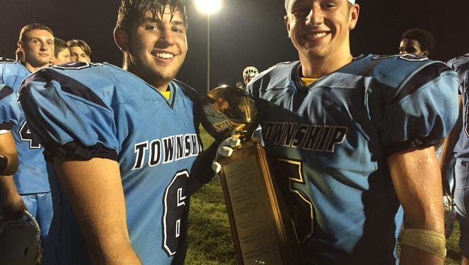 Freehold Township's Charles Sabbagh (left) and Anthony Lotti hold the Duke Trophy after the Patriots' victory.