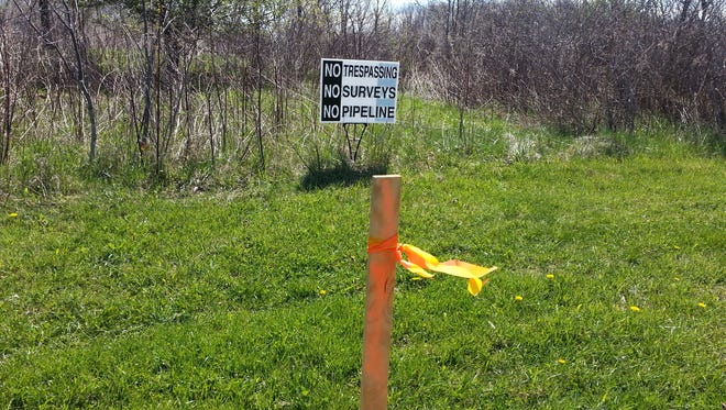 A sign of opposition to the proposed Nexus natural gas pipeline was placed by project opponent Jonathan Strong on his property near Medina, Ohio last year. In the foreground is a surveyor's stake marking the proposed route of the pipeline.