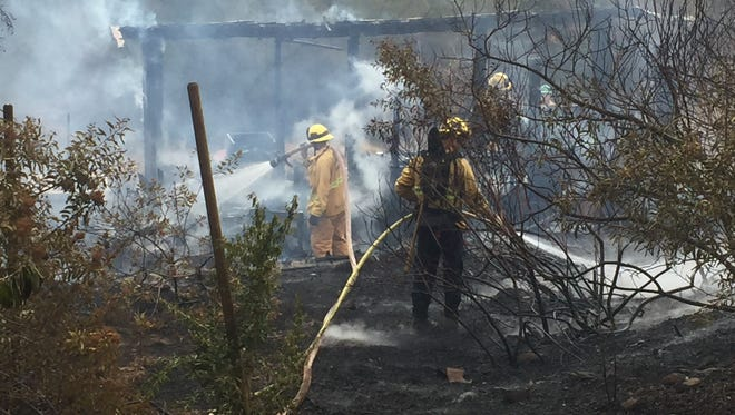 Firefighters battle a fire near Ojai on Tuesday morning that started in a structure and spread to nearby brush.