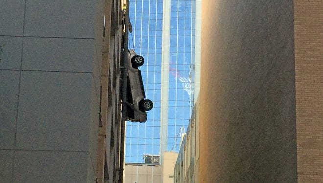 An SUV dangles from the side of a parking garage in downtown Austin, Texas, on Friday, Sept. 9, 2016. The driver safely escaped.