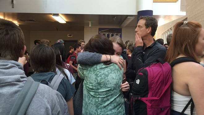 """Colleen Ellis hugs Ben Ellis' niece, Amanda, while Ben's brother, Bret, looks on after a singing dedicated to the former Fort Collins resident. Students at Fort Collins High School dedicated their weekly """"Singing on the Landing"""" to Ben, a Tenn. teacher originally from Fort Collins who was the subject of a viral video this month. Ellis died Thursday night."""