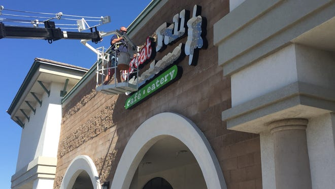 A worker begins installing the sign on the facade of the new Great Full Gardens in the Smith's center in south Reno. Opening is scheduled for the first week of October.