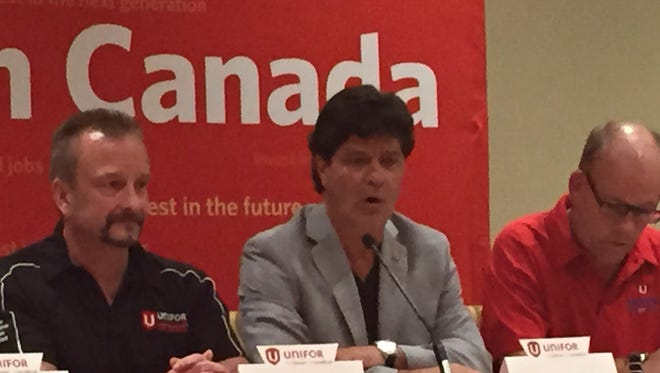 Unifor President Jerry Dias, center, flanked by Tim McKinnon, vice chair of Unifor's GM bargaiing committee and Greg Moffatt, chairman of Unifor's GM bargaining committee, announces a new tentative agreement with GM in Toronto on Sept. 20, 2016.