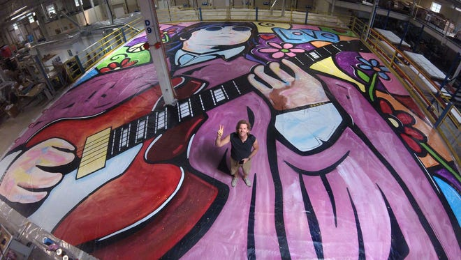 """Eric Waugh, who earned a Guinness World Record for creating the """"world's largest painting on canvas by a single artist"""" in 2003, painted his Lennon tribute, """"Imagine Again,"""" in Austin, Texas."""