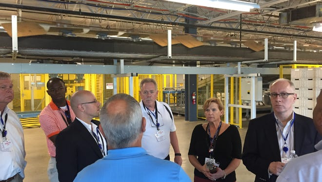 Jim Heck, Alex Burton, Jason Fertig, Ron Hagy, Lynn Miller-Pease and Greg Wathen listen as Jody Daniel of Walgreens leads a tour of the store's Anderson, S.C., distribution center.
