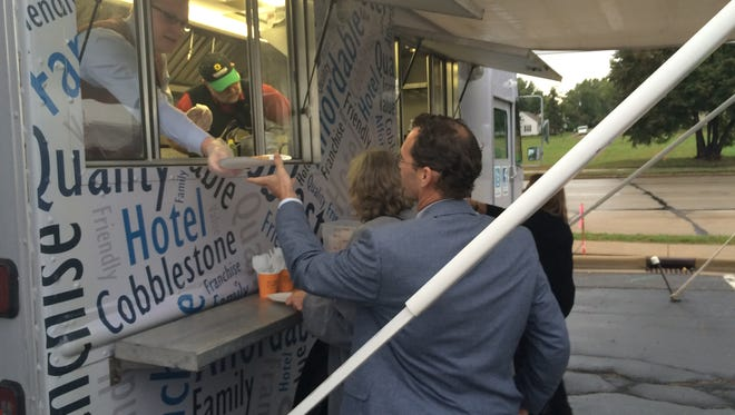 Cobblestone Hotel employees serve waffles out of a food truck following a groundbreaking ceremony for a new hotel in Stevens Point on Sept. 22, 2016.