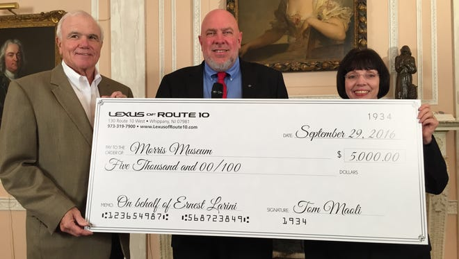 Ernest Larini, left, and Jim Totten, representing Celebrity motor Car and Lexus of Route 10 in Hanover, present a ceremonial check for $5,000 to Morris Museum Executive Director Linda Moore. Larini won a two-year Lexus lease in a museum golf outing and declined the car in favor of the donation to the museum.