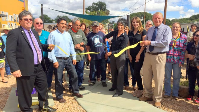 Life Quest CEO Debra Frasca cuts the ribbon during a ceremony Thursday afternoon to open up the Life Quest People's Park in Silver City.