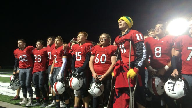 Pulaski senior Dominick Hendricks (No. 11) sings the school song along with his teammates on Friday following a 34-27 overtime victory against De Pere. Hendricks sustained a torn ACL in his right knee for a second time on Aug. 19 at Manitowoc.