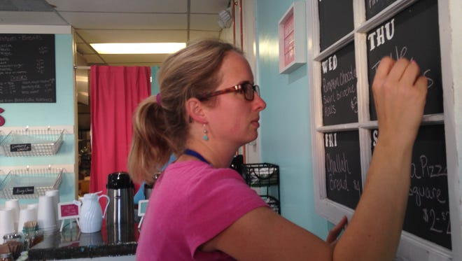 Beth Augustine writes daily specials on a chalkboard hanging inside her new Grand Ledge bakery Tuesday.
