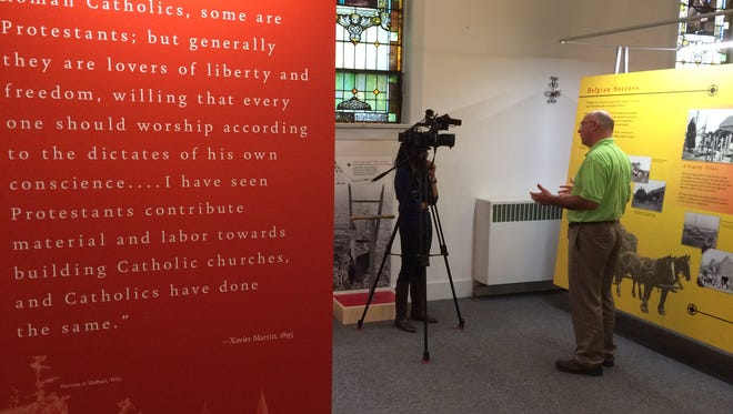 Bill Chaudoir, president of the Namur Belgian Heritage Foundation, talks with WLUK-TV reporter Gabrielle Mays while standing among the new historical exhibits at the Belgian Heritage Center.