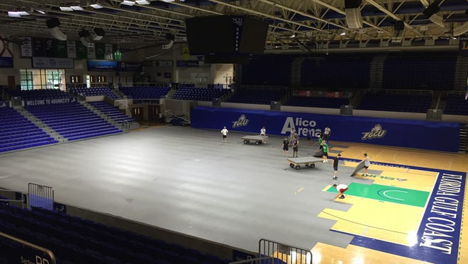 Workers disassemble the floor at FGCU's Alico Arena. The arenaserved as a shelter for Hurricane Matthew for people evacuating from the east coast.More than 200 spent the night there Thursday and early Friday morning.