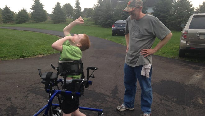 Isaac Wojnar raises his hands in the air while dad Jason watches as he moves around the new paved walking path at his family's Charlotte house.