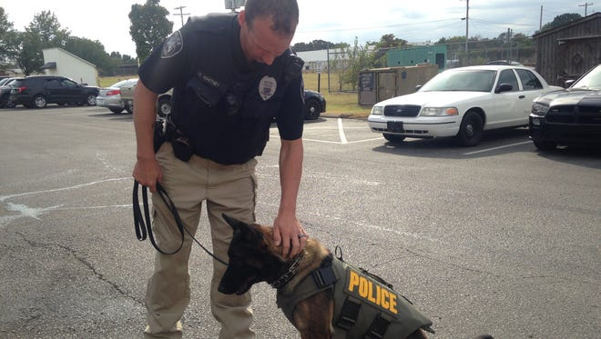 Oakley wears her new bullet and stab-protective vest before her shift starts with her handler, Lt. Kelvin Whitney.
