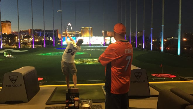 A golfer takes a swing at Topgolf Las Vegas, with The Strip as a backdrop.