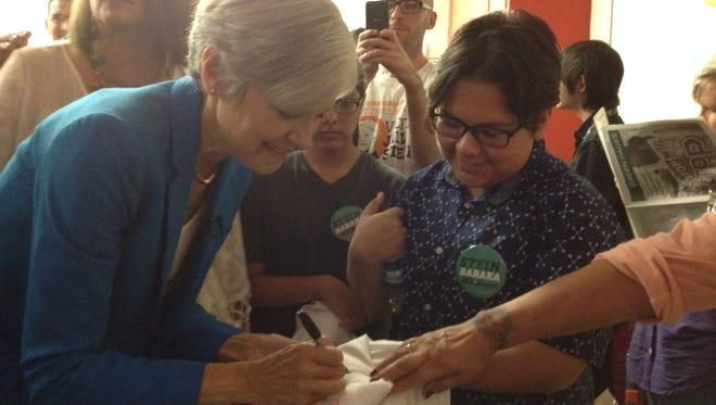 Green Party presidential candidate Dr. Jill Stein signs a shirt for Andy Mendez on Friday during a rally at Cafe Mayapan in El Paso.