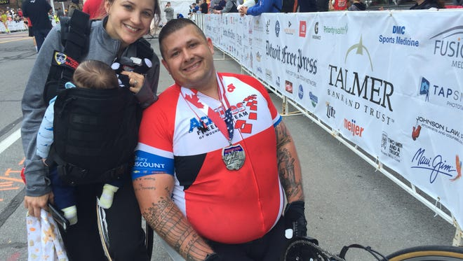 Michigan paralyzed veteran Nicholas Koulchar, who lost both legs in Iraq in 2008 and competed Sunday at the Free Press Marathon, with wife Dani and their 3-month-old son Finn.