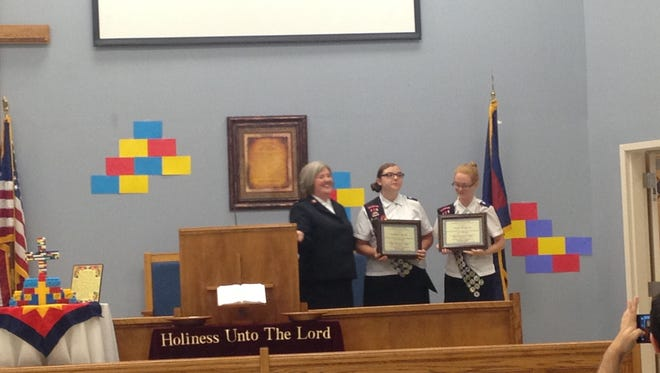 Salvation Army Maj. Jayne May presents the Catherine Booth Award to Madison Miller, middle, and Emma Brewster, right.