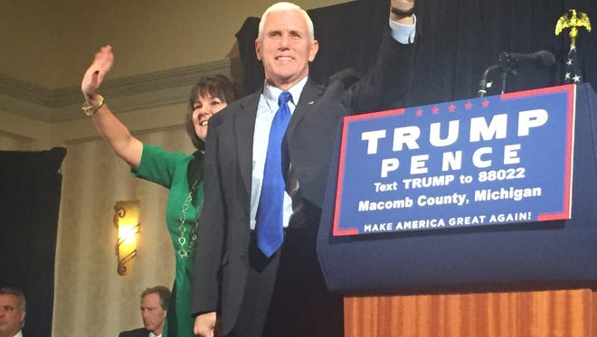 Republican vice presidential candidate Mike Pence and his wife Karen Pence greet a Macomb County audience Monday night.
