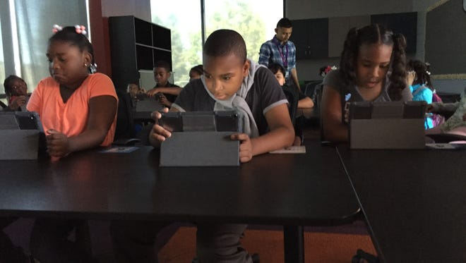 Students at the East Oakland Youth Development Center working with iPads.