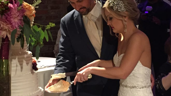 James P. Ezernack and Alanea Watson cut the wedding cake at their reception.