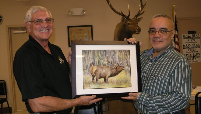 Joseph Romano (left), Exalted Ruler of Vineland Elks Lodge No. 1422, accepts a painting of an elk from artist George Perez.