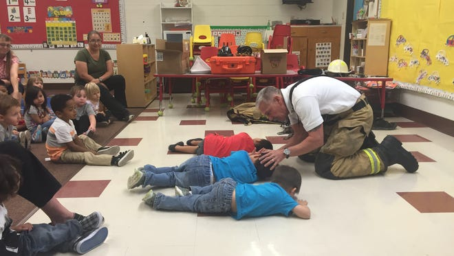 Fire marshal John Miller teaches students at Emmitt Smith preschool how to stop, drop and roll.