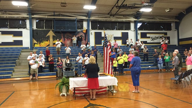 People stand for the Star Spangle Banner before a night of politicking in Bonifay, FL