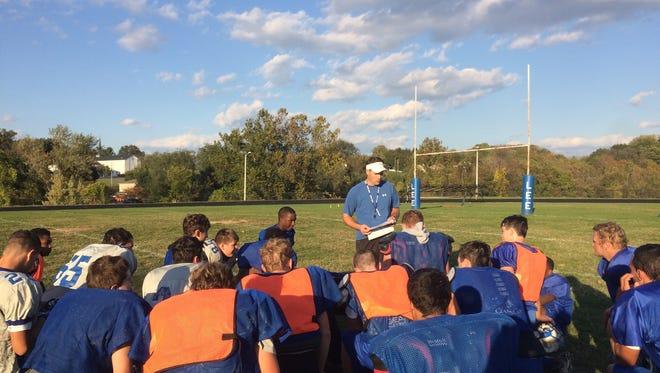 Lee High football coach Scott Girolmo addresses his team following practice Monday.