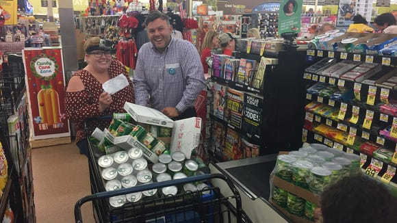 Megan Wyatt and David D'Aquin of The Daily Advertiser watch as a cashier rings up groceries they collected during the inaugural Supermarket Sweep competition Oct. 26 at Albertsons in Lafayette. The team collected three grocery carts of groceries  in under five minutes during the competition, which benefits Second Harvest Food Bank.