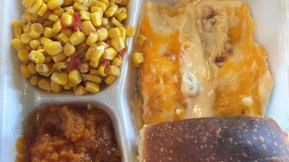 Crawfish enchiladas, corn maque choux, sweet potato casserole and a roll are pictured from Papa T's Cafe in Lafayette.