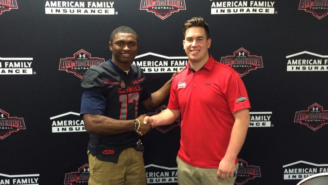 Oakland's JaCoby Stevens, left, accepts a jersey from Under Armour All-American Game's Corey Gibson.