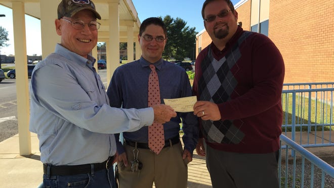 Presenting check is Bill Butler, UMWA Retiree, Joel Hettenhauser, Assist. Band Director and Kyle Payton, UC Band Director.