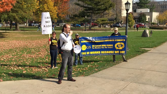 Landon Elkind, president of COGS UE Local 896, speaks Tuesday outside the Old Capitol shortly before the union presented its initially bargaining proposal to the University of Iowa and the Iowa Board of Regents. COGS represents about 2,200 graduate employees on campus.