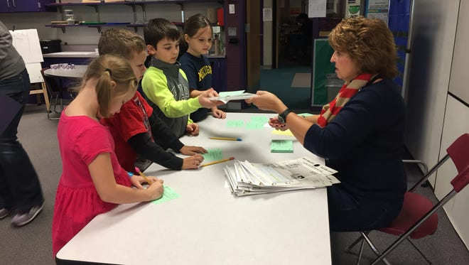 Marion Township Clerk Tammy Beal hands out ballots and secrecy slips for elementary students to use in a mock election Friday, Oct. 28. Students  discussed the importance of voting.