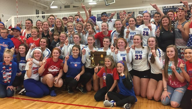 The Highland volleyball team poses with its fans after winning the Division III regional championship over Huron Saturday at Lake High School.