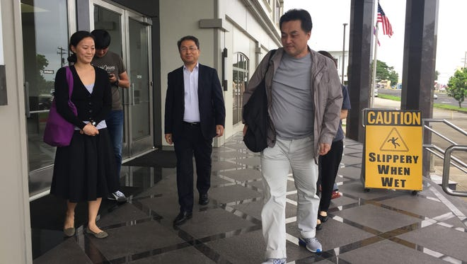 Kwon Woo Sung, right, a dentist from South Korea, leaves the District Court of Guam Monday afternoon after his sentencing hearing. He has pleaded guilty to interfering with flight attendants.