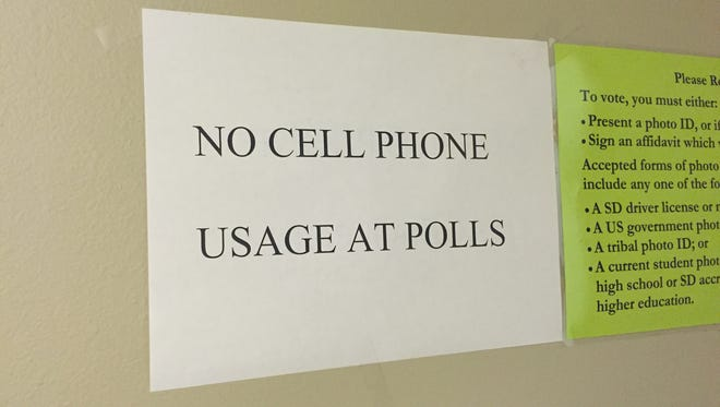"""A """"No cell phone usage at polls"""" sign hangs at the Lord of Life Lutheran Church polling location in eastern Sioux Falls on Election Day, Nov. 8, 2016."""
