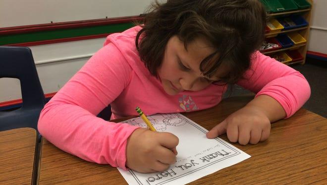 Sevastopol fourth-grade student Elizabeth Flok works on writing a letter to a U.S. soldier.