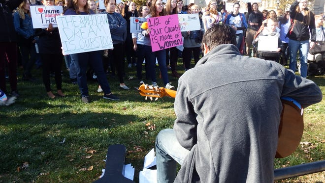 "Mike Roberts, an Iowa City resident, plays his guitar and leads a crowd of about 200 people  at a ""love trumps hate"" rally on Wednesday, Nov. 9, 2016, on the University of Iowa's Pentacrest in Iowa City."