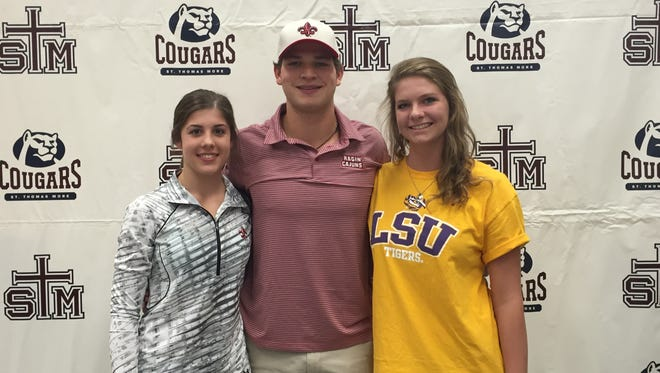 St. Thomas More's Avery Breaux, left, Alex Hannie, center, and Grace Horton after signing their national letters of intent. Breaux signed with UL volleyball, Hannie with UL baseball and Horton with LSU swimming.